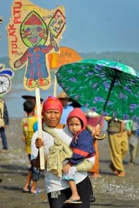 "Masyarakat Batang membawa wayang kertas serta membentangkan tulisan ""Food Not Coal"" sebagai aksi bersama Greenpeace menolak rencana pembangunan pembangkit listrik bertenaga batubara di Desa Ponowareng, Batang, Jawa Tengah, Selasa (23/9)."