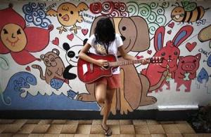 A girl practises the guitar during a free guitar workshop for street children in Manila