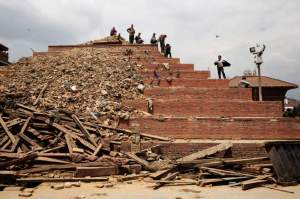 People atop damaged buildings in Durbar Square, Kathmandu, Nepal on April. 26, 2015. The historic Durbar Square, a UNESCO world heritage site, was severely damaged in an earthquake on April 25th. Photo by Adam Ferguson for Time