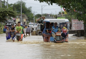 Residents wade through a flooded street after heavy rain at Candaba town, Pampanga province, north of Manila, December 17, 2015. Nine people were killed and hundreds spent the night huddled on their roofs in the central Philippines as floods generated by a powerful typhoon inundated villages, disaster officials said on Wednesday. REUTERS/Czar Dancel EDITORIAL USE ONLY. NO RESALES. NO ARCHIVES.